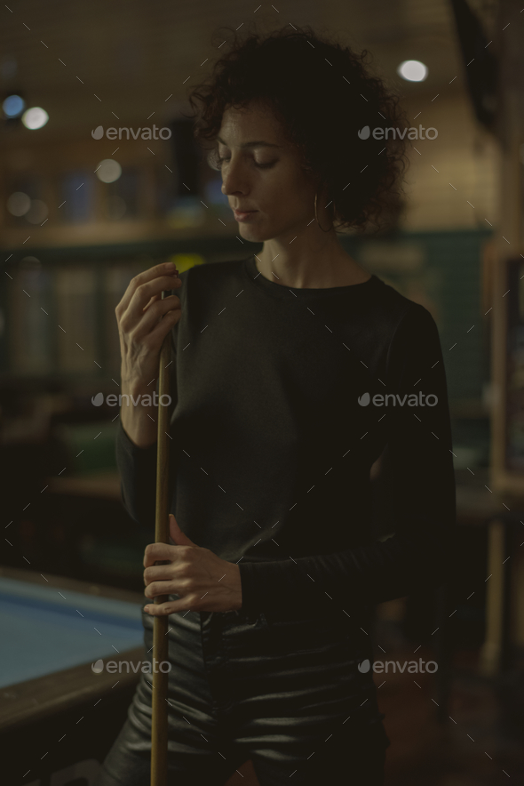 Woman playing pool at a bar - Stock Photo - Images