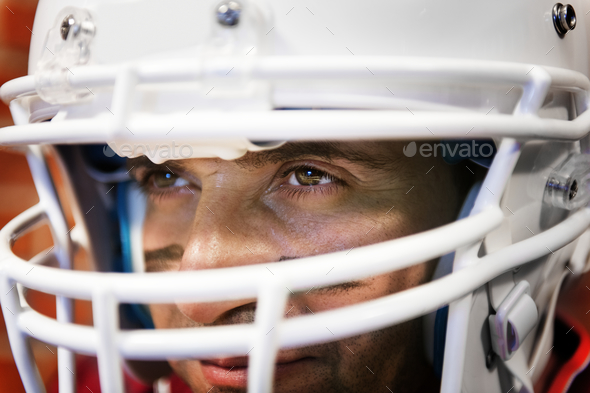 Man wearing Amerian football helmet - Stock Photo - Images
