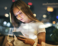 Serious young woman using a smartphone at a rooftop bar in the e - PhotoDune Item for Sale