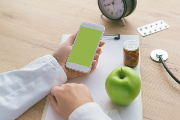 Doctor advising apple instead of pills and antibiotics - Stock Photo - Images