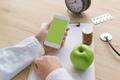 Doctor advising apple instead of pills and antibiotics - PhotoDune Item for Sale