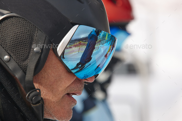 Ski goggles on a white winter landscape. Blue reflection. Horizontal - Stock Photo - Images