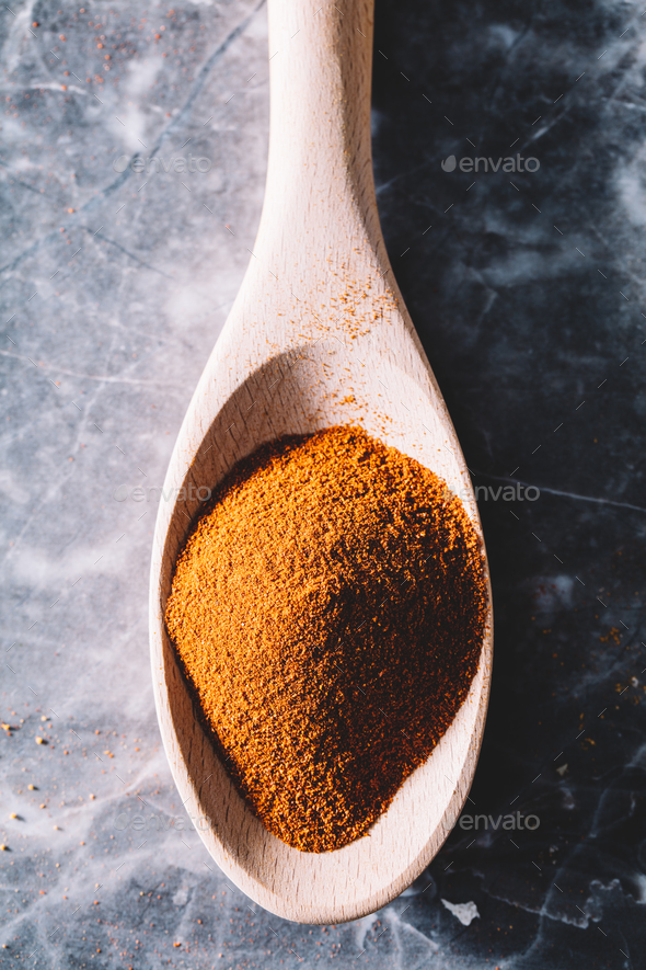 Single spoon with chili spice on marble background. - Stock Photo - Images