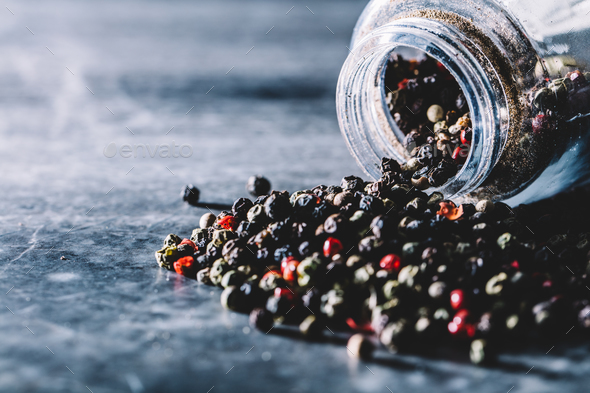 Grains of pepper spilling out of glass jar. - Stock Photo - Images