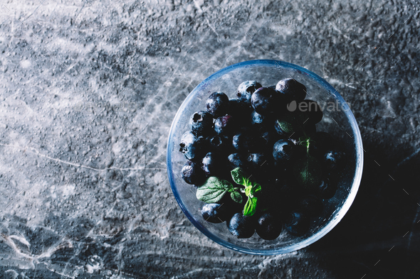Bowl of juicy blueberries with a green leaf - Stock Photo - Images