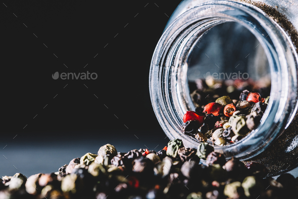 Mixed peppercorns spilling from a glass jar - Stock Photo - Images
