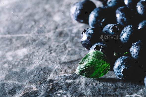 Fresh juicy blueberries and a green leaf - Stock Photo - Images