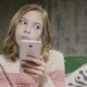 Young Girl Holding Phone in Hands Sitting in Room - VideoHive Item for Sale