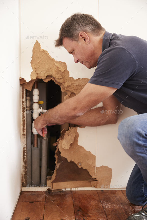 Middle aged man repairing burst water pipe, vertical - Stock Photo - Images
