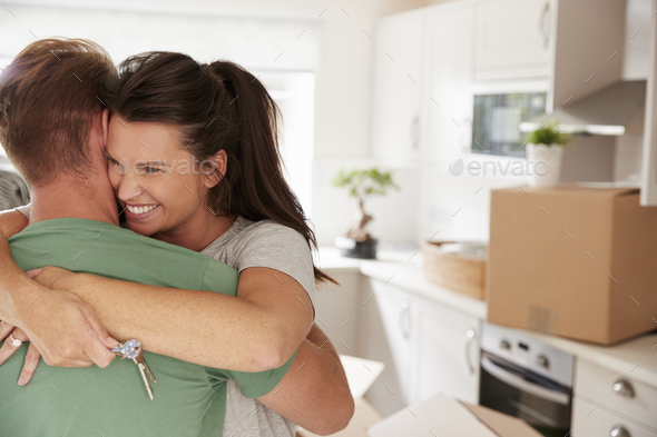 Hugging Couple Celebrating Moving Into New Home - Stock Photo - Images
