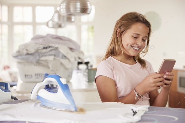 Young girl using distracted by phone while ironing - Stock Photo - Images