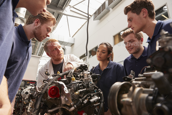 Mechanic showing engines to apprentices, low angle - Stock Photo - Images