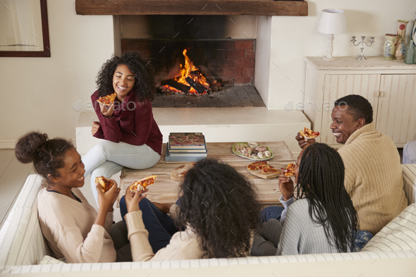 Family Sitting On Sofa In Lounge Next To Open Fire Eating Pizza - Stock Photo - Images