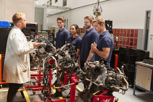 Apprentices studying car engines with a mechanic - Stock Photo - Images
