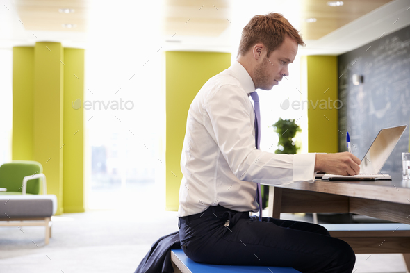 Businessman using laptop in an office meeting area, close up - Stock Photo - Images