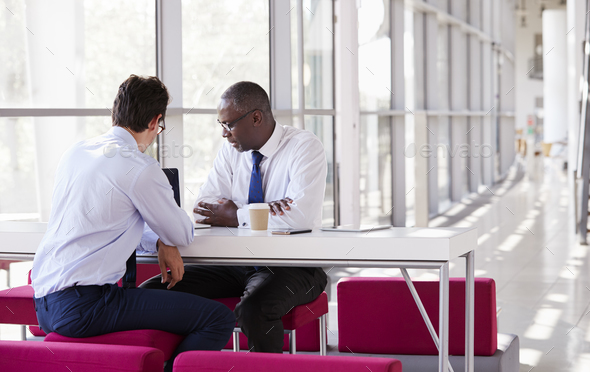 Two businessman look at laptop screen during a meeting - Stock Photo - Images