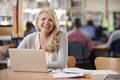 Portrait Of Mature Female Student Using Laptop In Library - PhotoDune Item for Sale