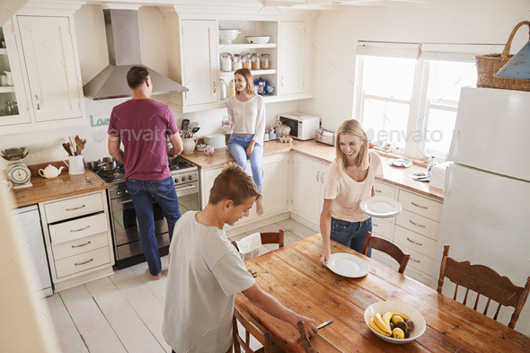 Family With Teenage Children Laying Table For Meal In Kitchen - Stock Photo - Images