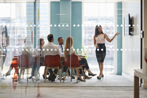 Female boss shows presentation on screen at business meeting - Stock Photo - Images