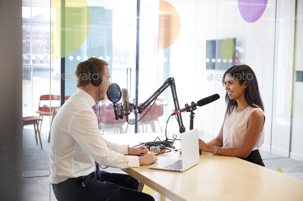 Young man interviewing a woman in a radio studio - Stock Photo - Images