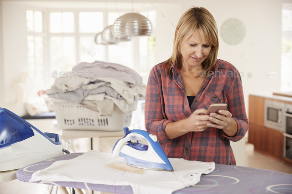 Middle aged woman distracted by phone while ironing t shirt - Stock Photo - Images