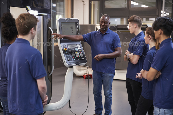 Engineer Showing Apprentices How To Use CNC Tool Making Machine - Stock Photo - Images