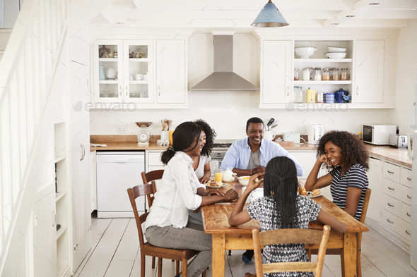 Family With Teenage Children Eating Breakfast In Kitchen - Stock Photo - Images