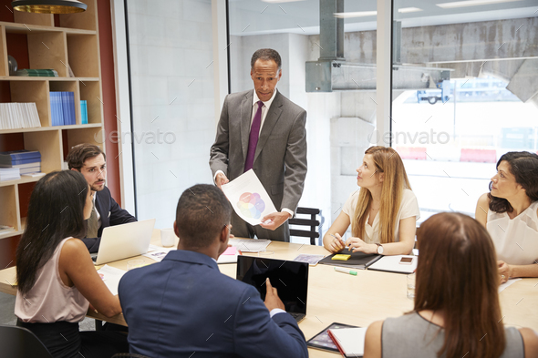 Male boss holding document at a business boardroom meeting - Stock Photo - Images