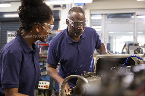 Engineer Showing Female Teenage Apprentice How To Use Lathe - Stock Photo - Images