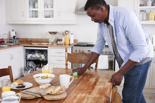 Man Clearing Breakfast Table And Loading Dishwasher - Stock Photo - Images
