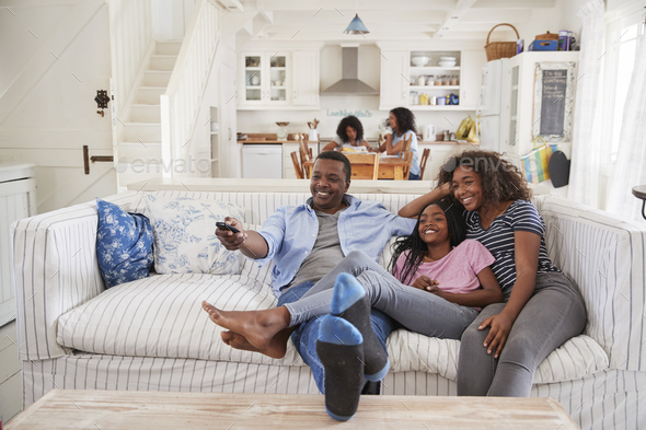 Father Sitting On Sofa Watching TV With Teenage Daughters - Stock Photo - Images