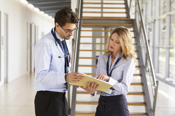 Young male and female doctors discuss notes at meeting - Stock Photo - Images