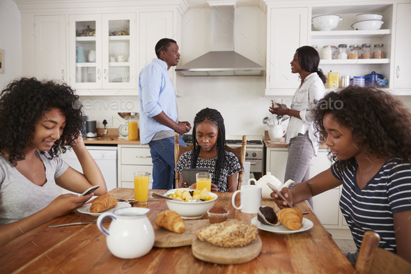 Family Sitting Around Breakfast Table Using Digital Devices - Stock Photo - Images