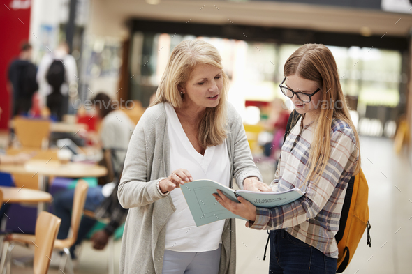 Teacher Talks To Student In Communal Area Of College Campus - Stock Photo - Images