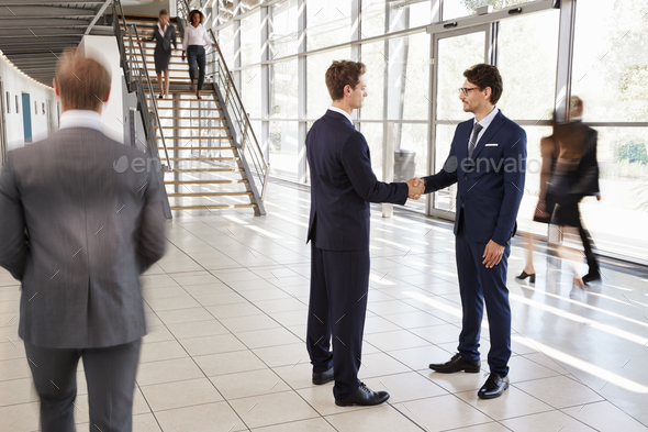 Two white businessmen shaking hands in a busy modern lobby - Stock Photo - Images