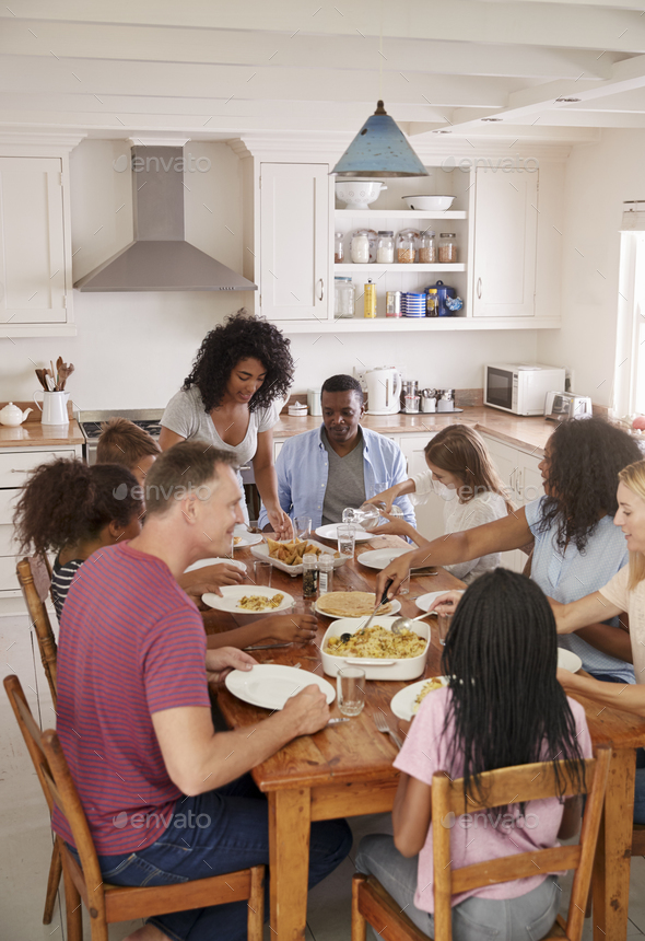 Two Families Enjoying Eating Meal At Home Together - Stock Photo - Images