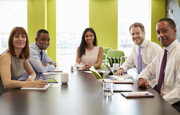 Business colleagues at an informal meeting look to camera - Stock Photo - Images