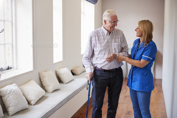 Nurse helping senior man walk using a walking stick - Stock Photo - Images