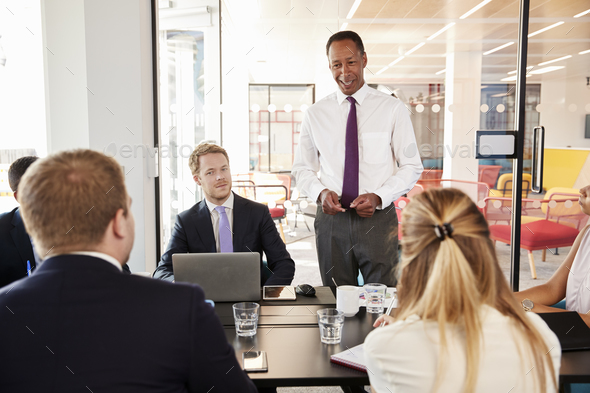 Black male manager addressing colleagues at a meeting smiles - Stock Photo - Images