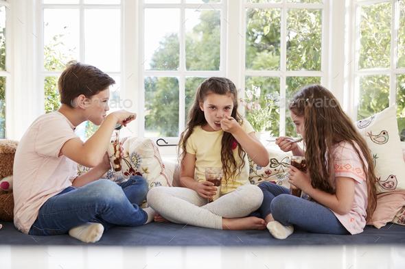 Children Sitting On Window Seat Eating Ice Cream Sundaes - Stock Photo - Images