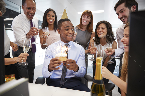 Colleagues gathered at a man's desk to celebrate a birthday - Stock Photo - Images