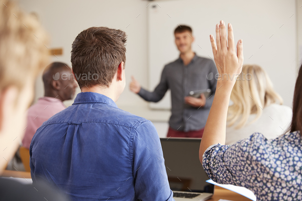 Rear View Of Mature College Student Asking Question In Class - Stock Photo - Images