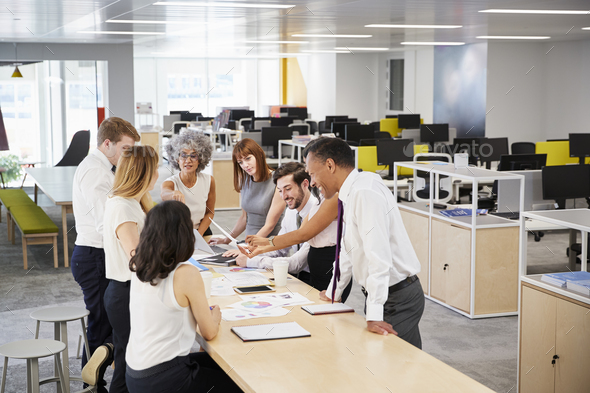Business team brainstorm in open plan office, elevated view - Stock Photo - Images
