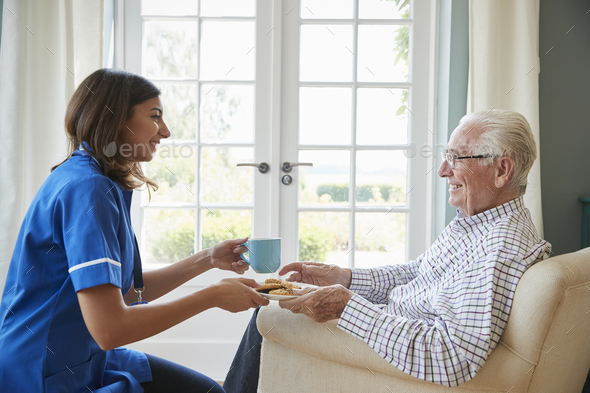 Nurse serving a cup of tea to a senior man at home, close up - Stock Photo - Images