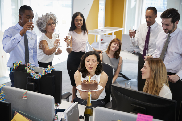 Colleagues gathered at woman's desk to celebrate a birthday - Stock Photo - Images