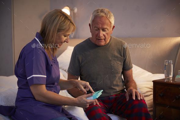 Nurse Helping Senior Man To Organize Medication On Home Visit - Stock Photo - Images