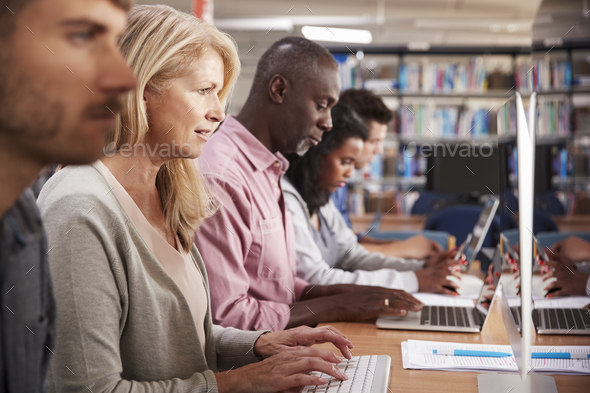 Group Of Mature College Students Working On Computers In Library - Stock Photo - Images