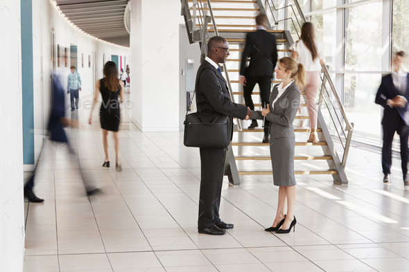 Businessman and woman shaking hands in a modern building - Stock Photo - Images