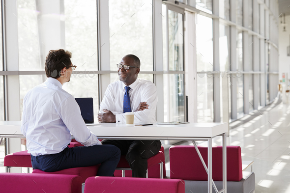 Two businessmen talk during a business meeting - Stock Photo - Images