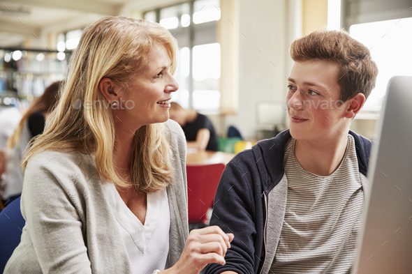 Teacher With Male Student Working On Computer In College Library - Stock Photo - Images